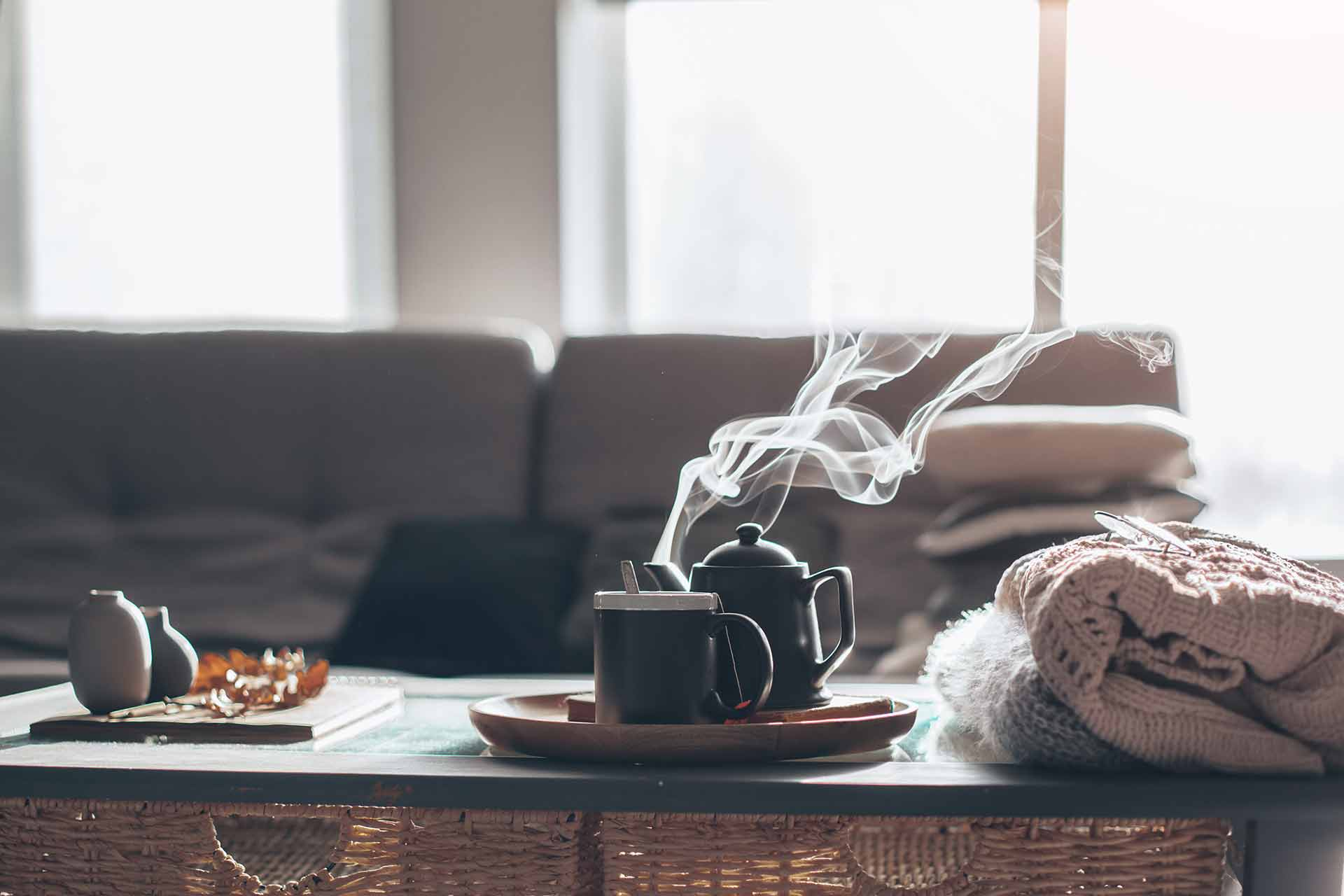 Ceramiczna zastawa na stole oraz dodatki w stylu hygge w salonie w stylu skandynawskim